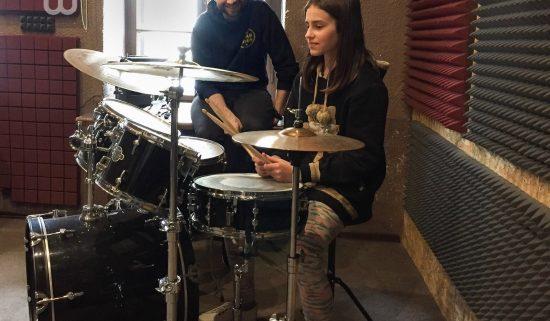 Девочка учится уграть на барабанах в музыкальной школе