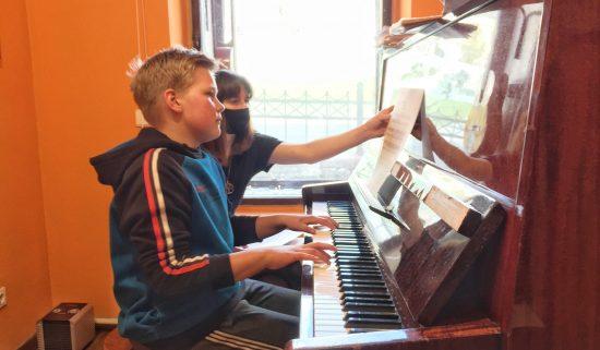 Мальчик учиться игре на пианино в музыкальной школе