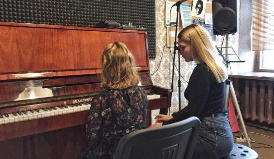 Преподаватель обучает ребенка игре на фортепиано