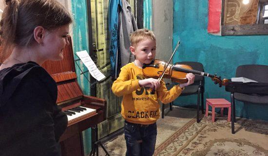 Мальчик учится играть на скрипке в музыкальной школе