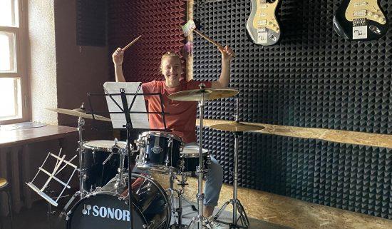 Девушка учится играть на барабанах