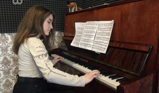 Девочка учится играть на фортепиано